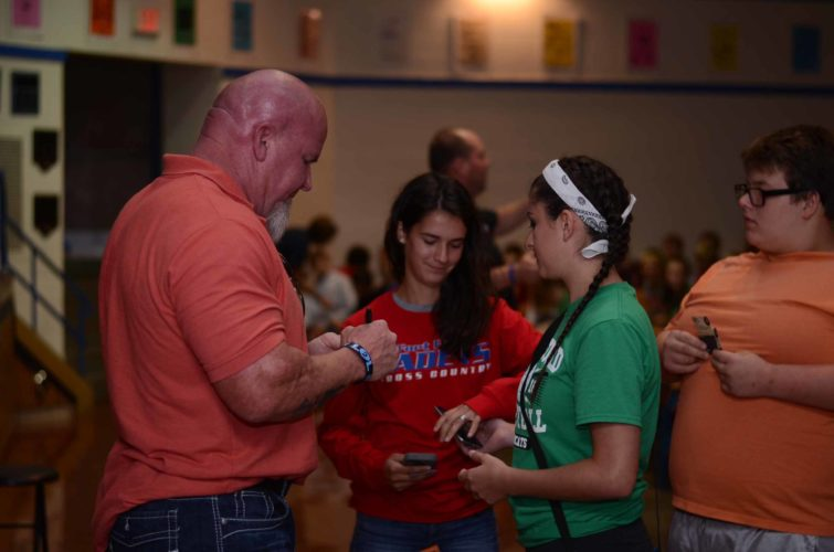 HANNAH KITTLE   The Marietta Times Mary Kate McElroy, 17, of Whipple, and Sarah Tilton, 17, of Lowell, meet two-time Olympian and Pro-Wrestler Chip Minton after his talk at Fort Frye High School on Tuesday.