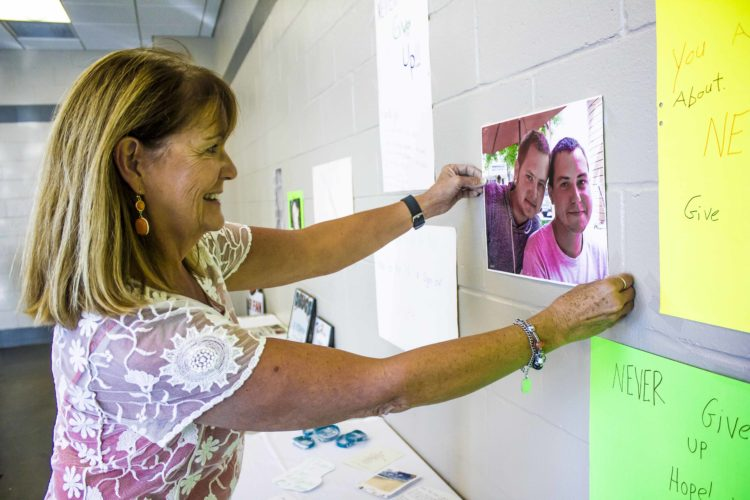 JANELLE PATTERSON   The Marietta Times Ginger O'Connor, 65, of Marietta, places a photo of her two nephews who passed away due to drug overdoses on the Honor and Recovery Wall at Marietta Municipal Court Tuesday. Andrew Morin, left, 27, died on Aug. 25, 2015, and Tyler Morin, 24, was found dead of an accidental overdose Aug. 10.