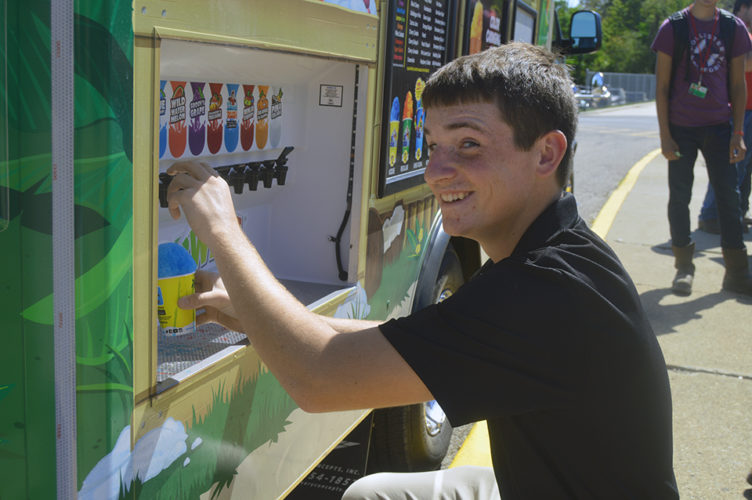 Richard Canterbury, a senior from Waterford in the Building Technology/Carpentry program, is having fun making his own flavored snow cone at the Flav-O-Wave area of the Kona Ice truck.