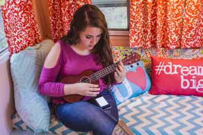 JANELLE PATTERSON    The Marietta Times Ellie Yeater, 14, of Williamstown, plays her ukulele in her renovated camper.