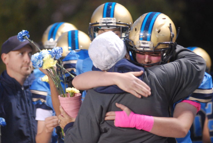 MIKE MORRISON The Marietta Times Frontier football player Jake Seevers, right, and cancer survivor Susan Schmidt embrace before the Cougars' game against Valley Wetzel Friday in New Matamoras.