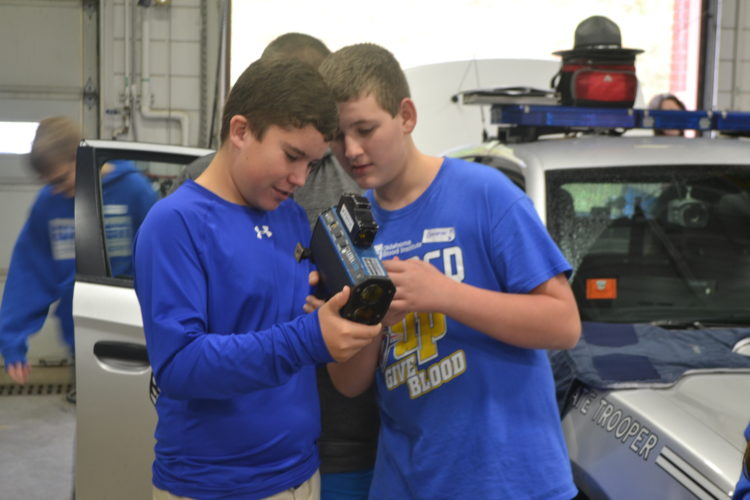 PEYTON NEELY   The Marietta Times Warren Middle School students Collin Welsh, 13, and Cameron Parvin, 12, check out the speed radar from the Ohio State Highway Patrol at YES Days on Friday at Washington State Community College.