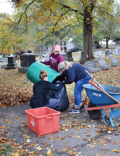Marietta College students Rachel Brown, 21, of Bridgeport, W.Va., Kali Miller, 20, of Carlton, Pennsylvania, and Elizabeth Dingey, 20, of Blue Rock, Ohio loaded leaves into a bag.