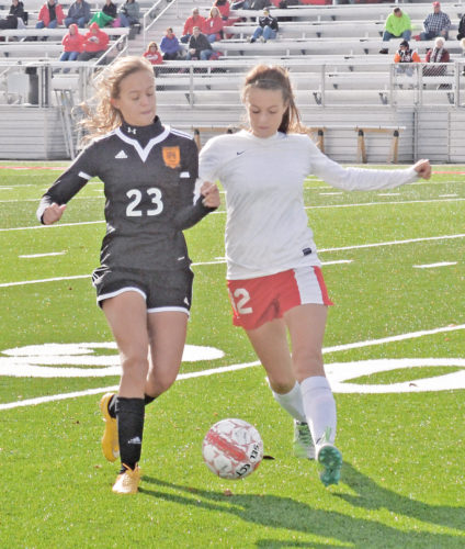 Marietta High's Jade Prescher (23) and Jackson's Cheirstynn Cooper, right, battle for the ball during Division II sectional-final action at Jackson Saturday. The Tigers lost 2-1 in overtime. Photo by Ron Johnston.