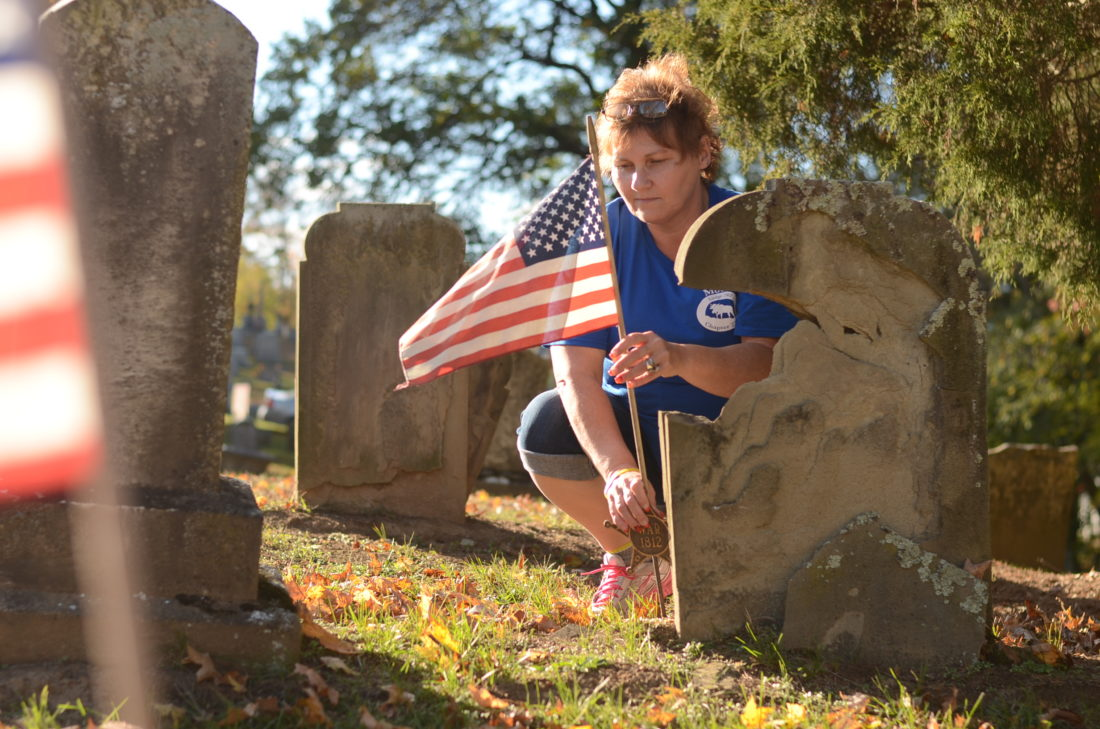 HANNAH KITTLE   The Marietta Times Tina LeMasters, officer of the Women of the Moose who is also heading up the project, adjusts a flag for one broken headstone at the Greenlawn Cemetery in Lowell on Monday.