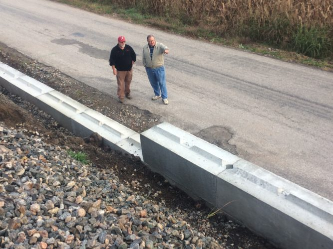 JANELLE PATTERSON   The Marietta Times Muskingum Township Trustee Gary Doan, left, shows former trustee John Karas and a retaining wall built out of concrete blocks by CSX this month to prevent further slippage. Doan worked on the project for four years