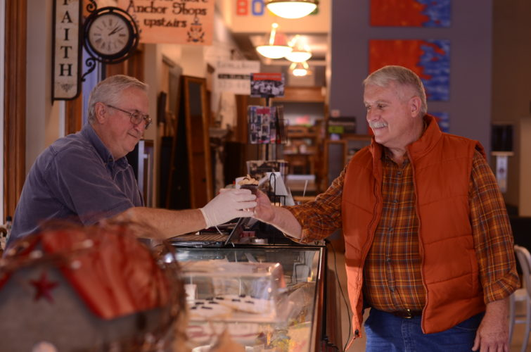 HANNAH KITTLE   The Marietta Times George Heidorn, the owner of Heidorn's Antiques at Putnam Commons, takes a moment to man the Village Cakery kiosk to sell Wyatt Graham, 62, of New Martinsville, W.Va., a peanut butter cupcake on Tuesday.