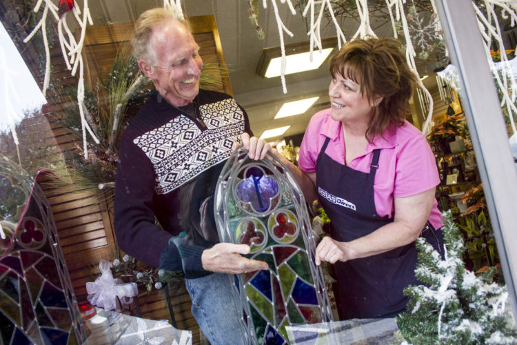 JANELLE PATTERSON   The Marietta Times Leo Anton, 69, of Marietta, helps Jan Shepherd, 55, of Marietta, place his uncle's stained glass windows in the storefront display of Two Peas in a Pod Friday.