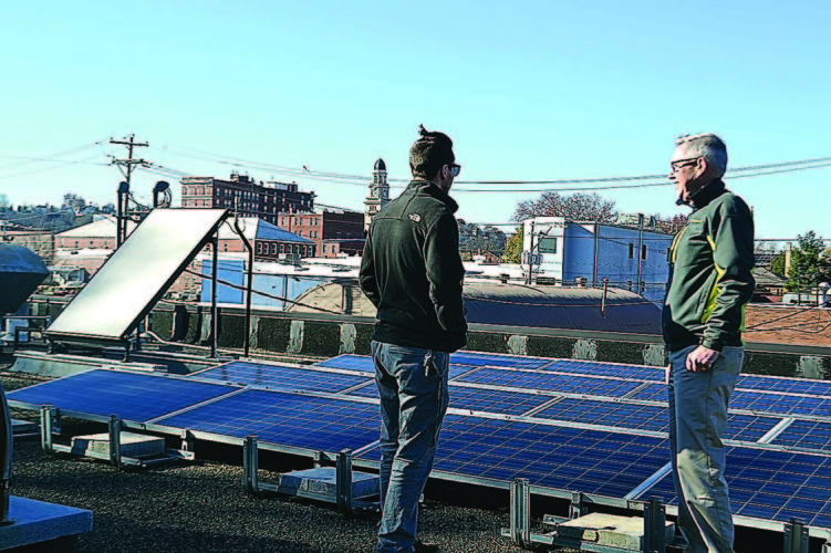 BRECKIN WELLS   The Marietta Times Fred Smith and Elliot Dodd examine the solar panels on the roof of the Pioneer House at Marietta College.