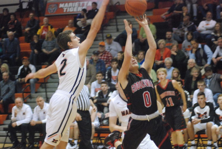 Marietta's Turner Hill (2) blocks the shot of Crooksville's Mike Baughman (0) during a high school basketball game Friday night at Sutton Gymnasium. Marietta won, 93-41.   JORDAN  HOLLAND  The Marietta Times
