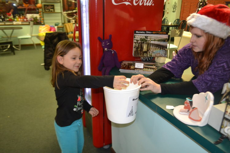 PEYTON NEELY   The Marietta Times Brooklyn Garrett, 4, of Little Hocking, picks out a snowball for a discount at Silver Linings on Front Street during the Merry-Etta Moonlight Savings Sale on Friday evening.