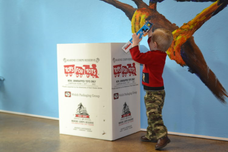PEYTON NEELY   The Marietta Times Damian Bond, 2, of Vienna, puts a toy into the Toys for Tots bin located at the Painted Sparrow on Monday afternoon.
