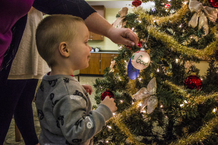 JANELLE PATTERSON   The Marietta Times Aden Karcher, 2, of Marietta, hangs an ornament in honor of his grandmother at Strecker Cancer Center in Marietta Monday.