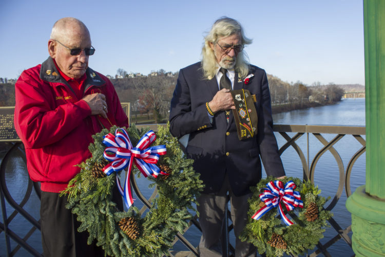 JANELLE PATTERSON   The Marietta Times Dave Smith and Bernie Cleveland pause for a prayer Wednesday before dropping wreaths in the Muskingum River to honor the fallen from the attack on Pearl Harbor 75 years ago.