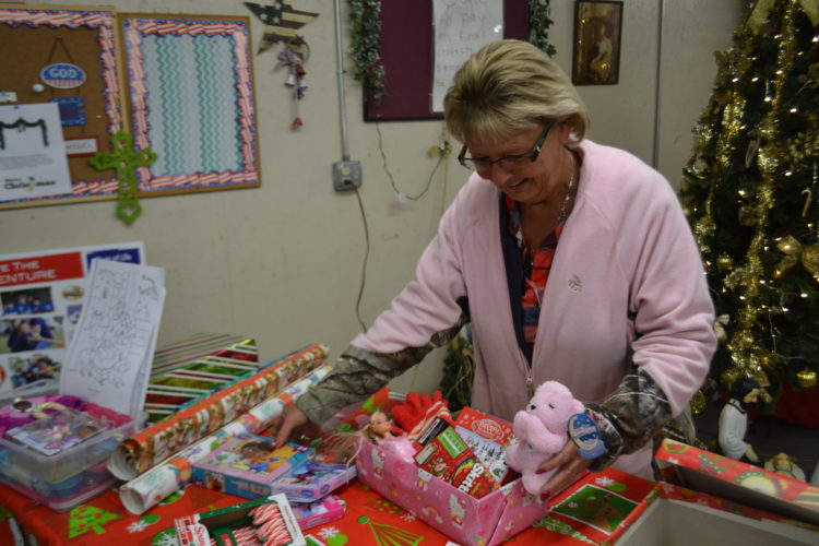 PEYTON NEELY   The Marietta Times Candy Waite, director of the Gospel Mission Food Pantry, fills a shoebox for a little girl for Operation Backyard Shoebox on Thursday morning.
