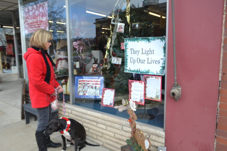 PEYTON NEELY   The Marietta Times Sylvi Caporale, owner of American Flags & Poles, and her rescue dog Tinkerbell look into the window of American Flags & Poles where the Light Up Our Lives tree is displayed Friday afternoon.