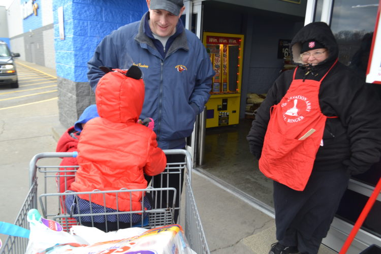 PEYTON NEELY   The Marietta Times Audrey Kesselring, 3, of Beverly, and her father Jared, 33, ring the bell for the Salvation Army Christmas Kettle at Walmart in Marietta next to veteran bell-ringer, Tava Douglas, 50, of Marietta, on Friday afternoon.
