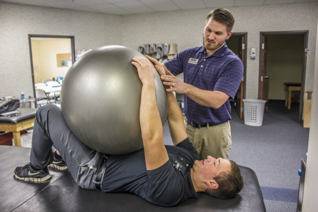 JANELLE PATTERSON   The Marietta Times  Andrew Robinson teaches physical therapy student Aleksey Lavrinenko exercises to reduce back pain at First Settlement Physical Therapy Wednesday.