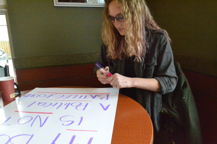 """PEYTON NEELY   The Marietta Times Madeline Gray, 22, of Marietta, makes a poster she will be using while participating in the Women's March on Washington at Tim Horton's in Marietta on Wednesday. Her sign said """"My body is not a political battleground."""""""