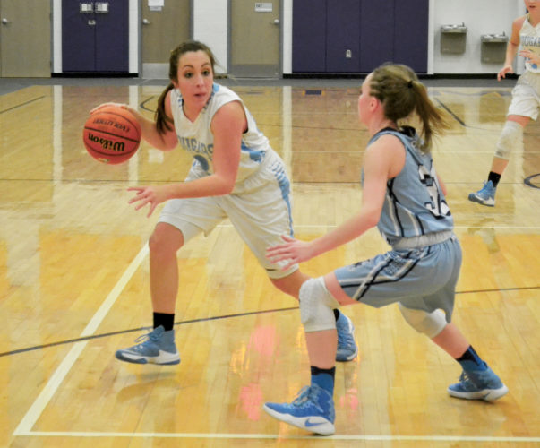 RONJOHNSTON, The Marietta Times Frontier's Sammi Morris (23)drives to dribble aroundParkersburg Catholic's Madeline Huffman (31)to get to the hoop during the Cougars' 50-40 victory over the Crusaderettes Thursday at St. Marys High School.
