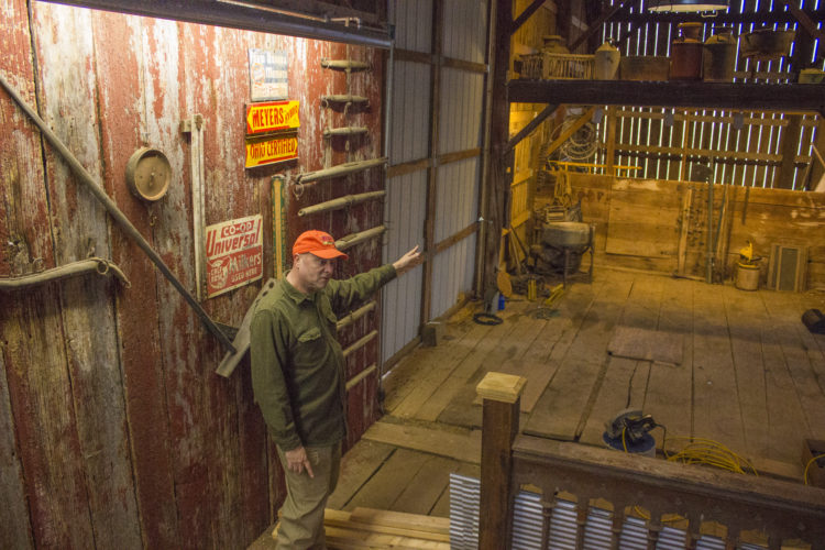 JANELLE PATTERSON   The Marietta Times Rick Shriver, 62, of McConnelsville, stands in front of a historic farm tools display as he explains where he plans to put the bar in his barn at Willis Hill Farm in McConnelsville Monday.