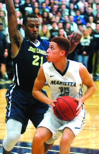 JORDAN HOLLAND The Marietta Times Marietta College's Nate Walker, right, makes a move with the ball during a college men's basketball game against John Carroll at Ban Johnson Arena.