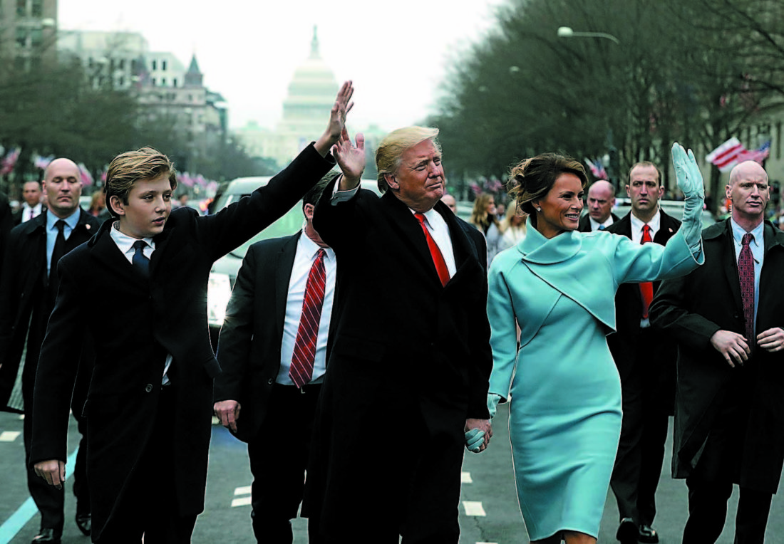 President Donald Trump waves as he walks with first lady Melania Trump and their son Barron during the inauguration parade on Pennsylvania Avenue in Washington, Friday, Jan. 20, 2016. (AP Photo/Evan Vucci, Pool)