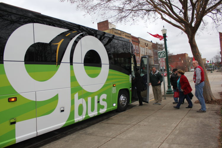 JANELLE PATTERSON   The Marietta Times GoBus Manager Rob Goebel, left, welcomes Steve Thomas, center, Kathy Downer, and Andy Coleman, right, onto the GoBus in front of the Armory Thursday.