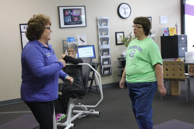 JANELLE PATTERSON   The Marietta Times Curves coach Diane Erb, left, works with Marjorie Offenberger, center, of Williamstown, and Nancy Coulter, right, of Williamstown, during a body balance class at the Curves facility in Marietta Wednesday.