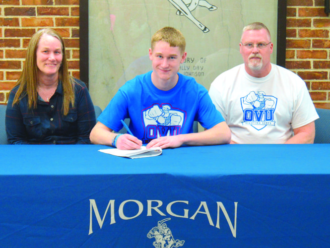 Courtesy photo Morgan's Jordan Work, center, signs a National Letter of Intent to play soccer at Ohio Valley University last week in McConnelsville. He is joined by father David Work and mother Lori Work.