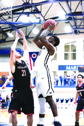 Photo courtesy of Nate Knobel Marietta College's A.J. Edwards, right, goes up for a basket as Muskingum's Rickey Wilson defends during a college men's basketball game Wednesday night at Ban Johnson Arena.