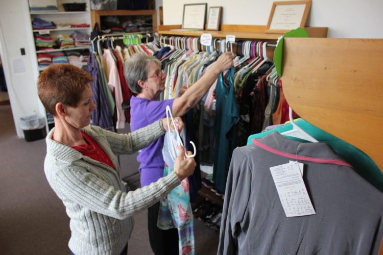 Sheri Neill, 59, and Carol Stollar, 69, both of Waterford, hang clothes at the Waterford Church of the Nazarene in preparation for Thursday's free closet from 9 to 11 a.m.  JANELLE  PATTERSON    The Marietta Times