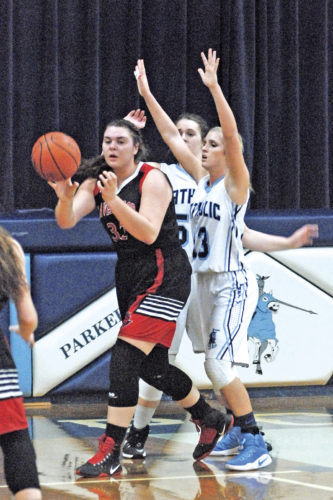 Ravenswood's Ali Westenhaver (32) passes to a teammate as Parkersburg Catholic's Alexis Saunders (13) defends during a high school basketball game Tuesday in Parkersburg. Photo by Steve Hemmelgarn.