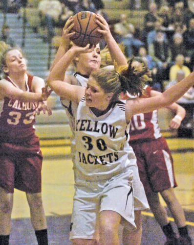 Williamstown's Bethany Wager (33) and Bethany Arnold (44) behind Bethany Wager secure a rebound together during the Yellowjackets' 96-51 Class A Region IV, Section 1 semifinal win Tuesday night over Calhoun County. Photo by Joe Albright.