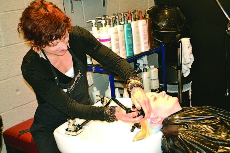 PEYTON NEELY   The Marietta Times Anne Gray, owner of Serenity Now in Marietta, washes out the hair dye on Mariah Carper, 27, of Reno, at her shop earlier this week.