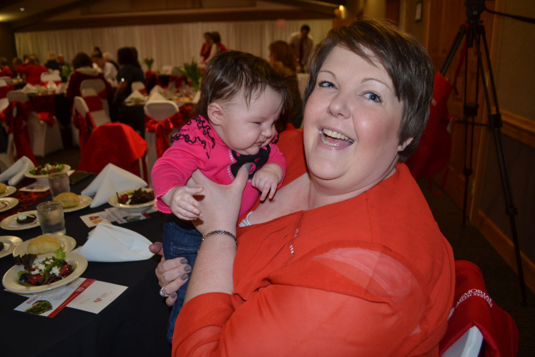 ERIN O'NEILL  The Marietta Times Tisha Chichester of Marietta holds her 3-month-old niece, Taylor Schaad, during the Cardiac Conversations Sweetheart Luncheon at the Marietta Shrine Club Thursday. Chichester and her mother, Belinda Schaad, and sister-in-law, Tamara Schaad, were at the luncheon to support Donna Hutchinson, the baby's great-grandmother and a two-time heart attack survivor.