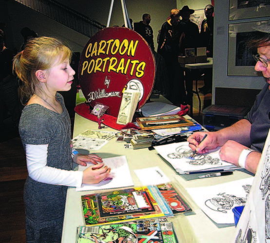 File photo Lynaea Oliver, 6, left, of Parkersburg, colors as she talks with artist J.D. Williamson at last year's Classic Plastics Toy and Comic Expo at the Parkersburg Art Center.