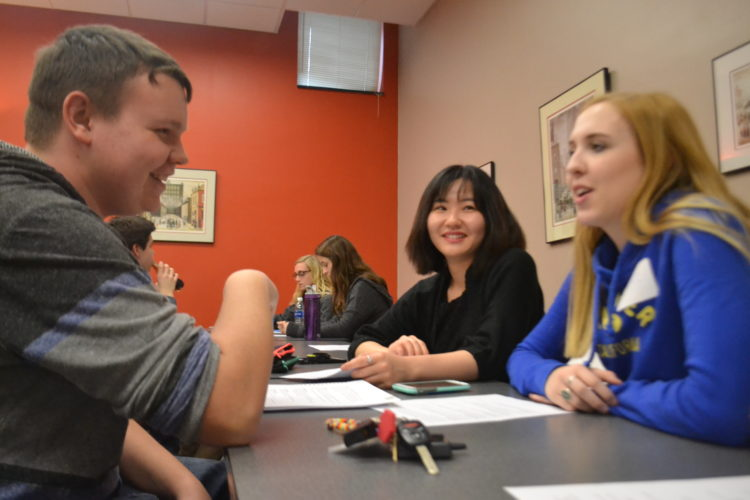 PEYTON NEELY   The Marietta Times Marietta High School senior Jackson Kelly, 18, works with Marietta College students Jane Peterson, 18, of Minot, N.D., and Hilary Hao, 21, of Bejing, China, at Marietta College during a peer mentorship class for the entrepreneurship classes at both the high school and the college.