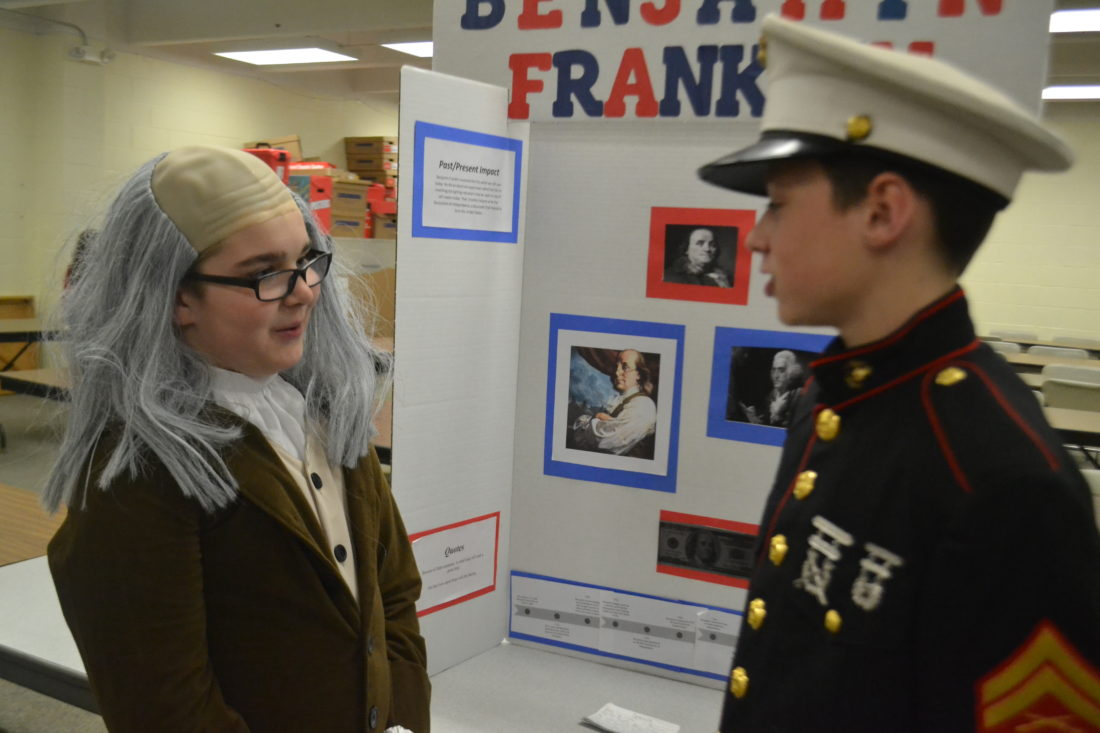 By Peyton Neely   The Marietta Times Riley Depuy, 11, dressed as Benjamin Franklin, talks with his friend Tommy Kerenyi, 12, who is dressed as Chesty Puller, during the Social Studies Fair at St. Mary School on Monday night.