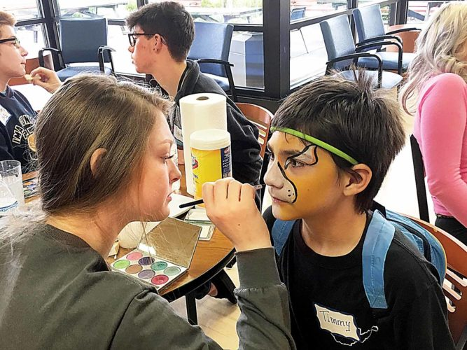 Michael Erb   Special to the Times Parkersburg High School student and volunteer Madi Gribble paints the face of Timmy Roberts, 12, a student from Edison Middle School, at an activity station Tuesday during the Artsbridge Very Spectacular Arts Festival at West Virginia University at Parkersburg.