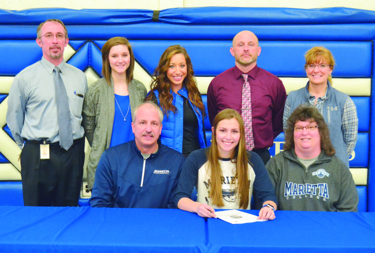 RON JOHNSTON The Marietta Times Warren senior Katie Rauch and Bishop Ford commited to continuing their athletic career at Marietta College Wednesday. Sitting, left to right: Brian Rauch (father), Katie, and Jenny Rauch (mother). Standing, left to right: Ben Cunningham (principal), Katie Farley (assistant coach), Arielle Baker (athletic trainer), Ryan Lemley (principal) and Deb Proctor (AD).