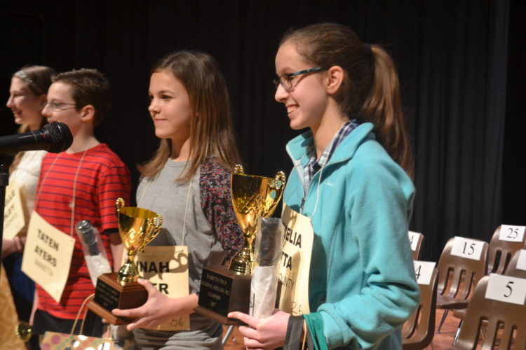PEYTON NEELY   The Marietta Times Cecelia Fatta, 14, right, from Jackson Middle School, smiles as she wins the 37th annual Marietta Times Regional Spelling Bee on Friday night. Standing next to her is the runner-up, Hannah Archer, 14, from St. Mary School.