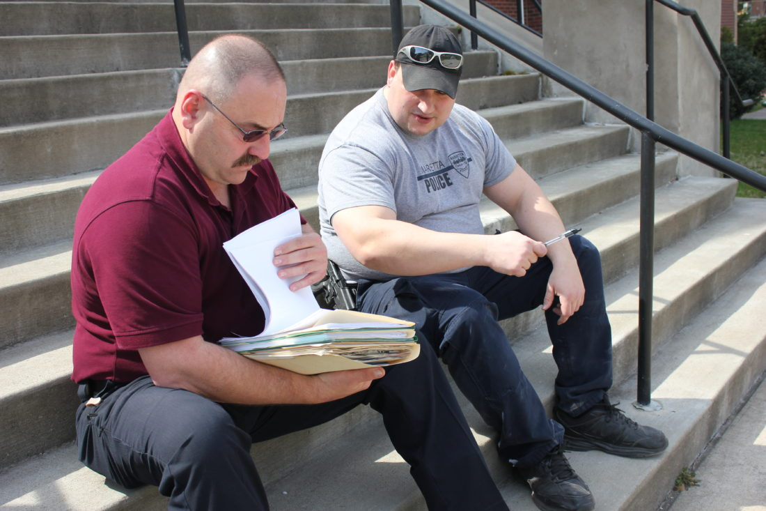 JANELLE PATTERSON   The Marietta Times Marietta Police Chief Rodney Hupp, left, and Capt. Aaron Nedeff review old files to be destroyed on Friday.