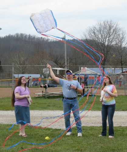 JEFFREY SAULTON  Special to the Times Ashley Wyant, left, and Aysia Randolph, right, watch as Scott Randolph, center, tries to  get a kite aloft at the kite fest.