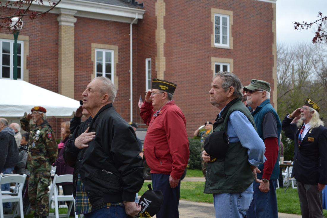 ERIN O'NEILL   The Marietta Times Servicemen and women and community members salute as the American flag is raised during the National Vietnam Veterans Day event at the armory in Marietta Wednesday.