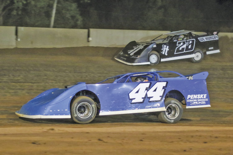 Colten Burdette (44) goes low while Tyler Carpenter (28) attempts to pass on the outside during Friday night's AMRA Late Model feature at the Legendary Hilltop Speedway. Burdette held on to grab the win while Carpenter finished fourth. Photo courtesy of Zach Yost.