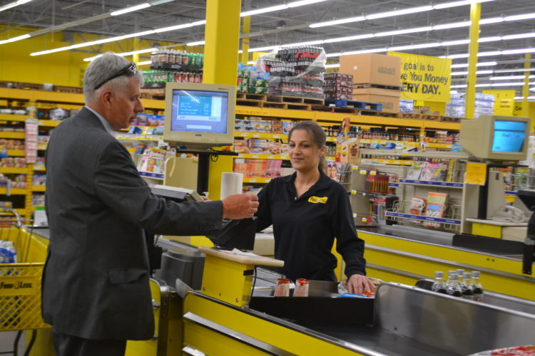 PEYTON NEELY   The Marietta Times Julie Angeron, 30, cashier at Food 4 Less, scans products being purchased by Marietta resident George Broughton, 59, on Monday at the Marietta store.