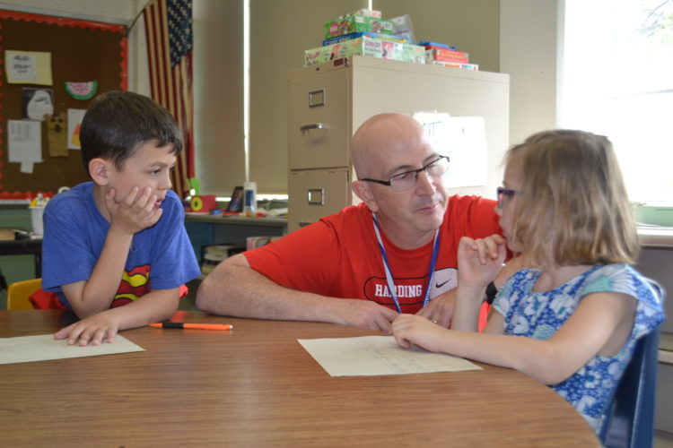 PEYTON NEELY   The Marietta Times P.E. teacher Mark Daughety, center, helps kindergartener Jocelyn Evans, 6, as Aiden Lipscomb, 6, listens in at Warren Elementary School on Tuesday.