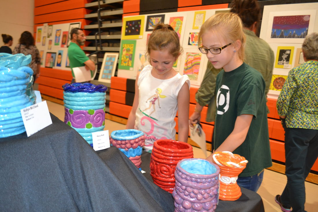PEYTON NEELY   The Marietta Times Phillips Elementary third-grader Brooke Hall, 9, left, and Marietta Middle School student Cassidy Graham, 12, look at art displayed at the Marietta City Schools Fine Arts Festival on Wednesday evening in the high school's gym.