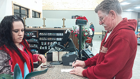 Photo by Jody Isaackson Employee Heidi Harris rang up Al Anderson's coffee as the first Cottonwood C-Store customer Friday morning. The new, larger facility offers 60 new products to its customers.